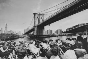 New York City's Brooklyn Bridge is seen looming over a sightseeing boat, July 3, 1964.